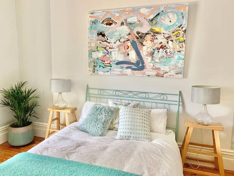 feminine styled bedroom in adelaide home with original painting like a kid in a candy shop on wall