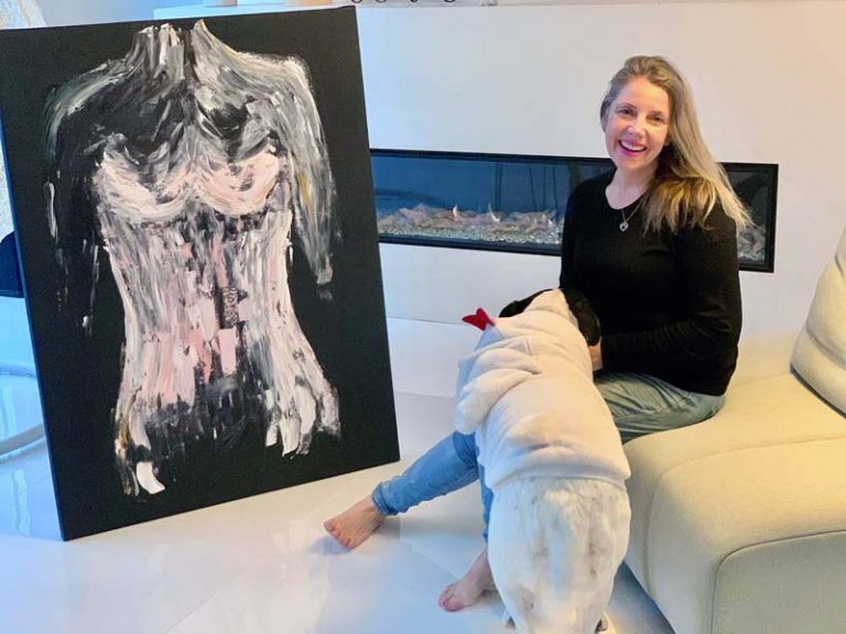 sarah jane artist with black canvas painting of a womans body in pink titled isolation ii